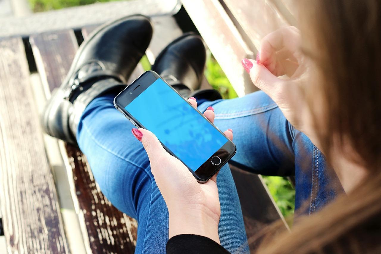 Nainen, jolla on kädessään iPhone-puhelin