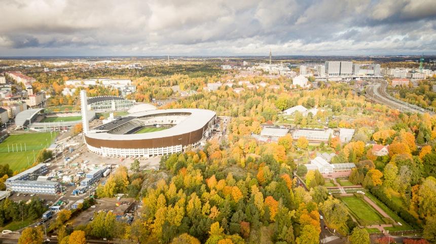 Dronekuva, jossa näkyy Olympiastadion ja syksyistä metsää